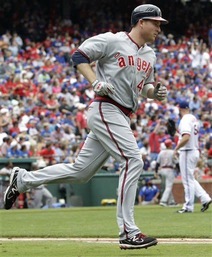 Los Angeles Angels' Mark Trumbo rounds first on his two-run home run off of Texas Rangers starting pitcher Matt Harrison, rear, in the fourth inning of a baseball game Saturday, May 12, 2012, in Arlington, Texas. The shot scored Torii Hunter. (AP Photo/Tony Gutierrez)