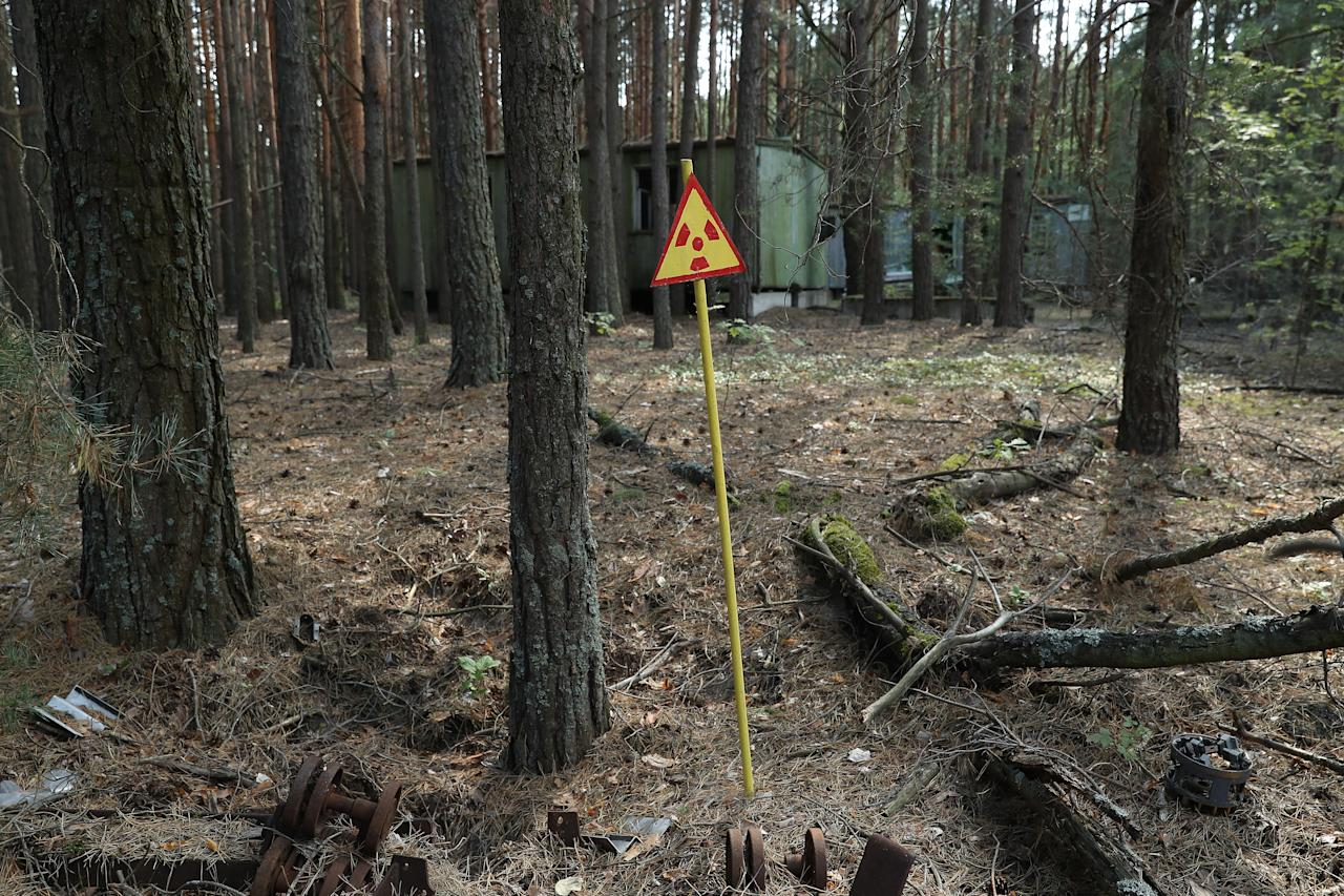 <p>A sign warns of radiation contamination in a forest in the abandoned city of Pripyat near the Chernobyl nuclear power plant on Aug. 18, 2017, in Pripyat, Ukraine. (Photo: Sean Gallup/Getty Images) </p>