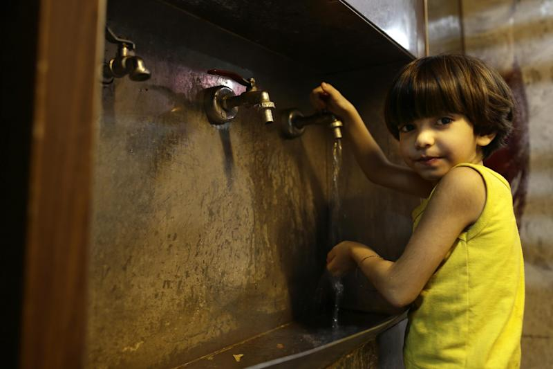 In this Sunday, Aug. 25, 2013 photo, a girl whose family fled their home because of Syria's civil war runs water for drinking in the kitchen of the Kertaj Hotel in Damascus, Syria. Around a dozen families living for months in the Kertaj Hotel and say it has become like a home to them. (AP Photo/Hassan Ammar)