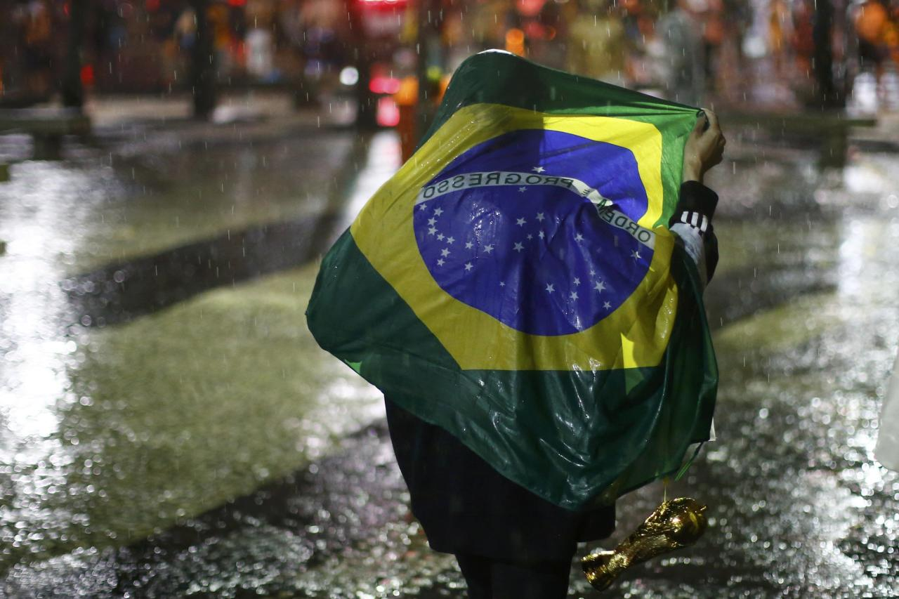 A Brazil soccer fan walks in the rain after watching a broadcast of their team's loss against Germany in their 2014 World Cup semi-final match, in Rio de Janeiro July 8, 2014. REUTERS/Jorge Silva (BRAZIL - Tags: SOCCER SPORT WORLD CUP)