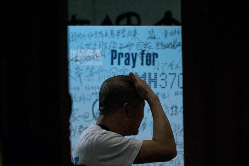 """One of the relatives of Chinese passengers on board Malaysia Airlines Flight 370 rubs his head near a board covered with written wishes from relatives during a briefing given by Malaysian officials at a hotel in Beijing, China, Wednesday, March 26, 2014. Some of the wishes, partially seen, read, """"Dear husband, you must stay strong, I am waiting for you. My dear, please be back soon."""" The search for the missing plane resumed Wednesday after fierce winds and high waves forced crews to take a break Tuesday. (AP Photo/Alexander F. Yuan)"""