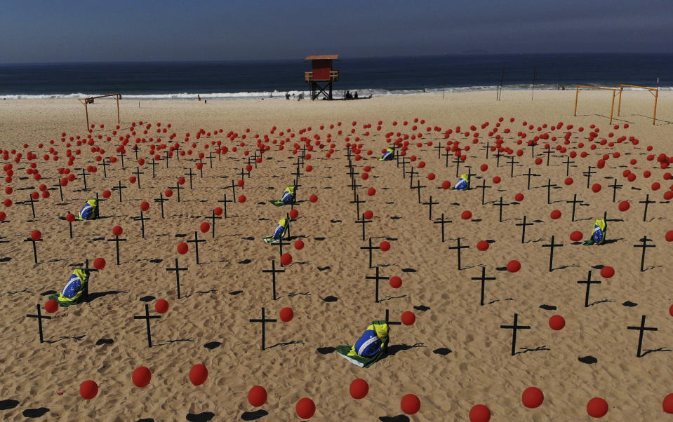Crosses and red balloons are placed in the sand on Copacabana beach in a demonstration organized by Rio de Paz to honor the victims of COVID-19, as the country heads to a milestone of 100,000 new coronavirus related deaths, in Rio de Janeiro, Brazil, Saturday, Aug. 8, 2020. (AP Photo/Mario Lobao)
