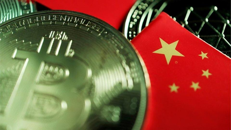 A real-world coin designed with the Bitcoin logo lies scattered on a table amid some miniature Chinese flags