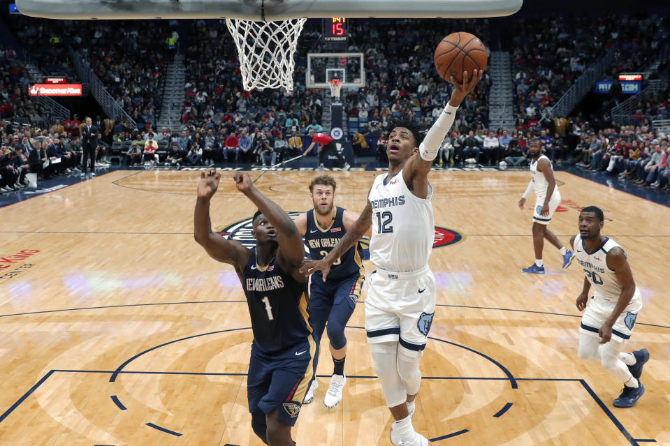 Memphis Grizzlies guard Ja Morant (12) goes to the basket against New Orleans Pelicans forward Zion Williamson (1) during the first half of an NBA basketball game in New Orleans, Friday, Jan. 31, 2020. (AP Photo/Gerald Herbert)