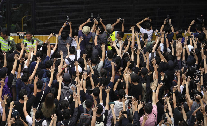 Supporters surround a police bus carrying political activist Edward Leung as it leaves the High Court in Hong Kong, Wednesday, Oct. 9, 2019. Several hundred masked protestors chanting for revolution have gathered at Hong Kong's High Court for the appeal hearing of an activist sentenced to six years in prison for his part in a violent nightlong clash with police. (AP Photo/Vincent Yu)