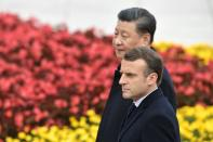 French President Emmanuel Macron walks with Chinese President Xi Jinping during a welcome ceremony at the Great Hall of the People in Beijing