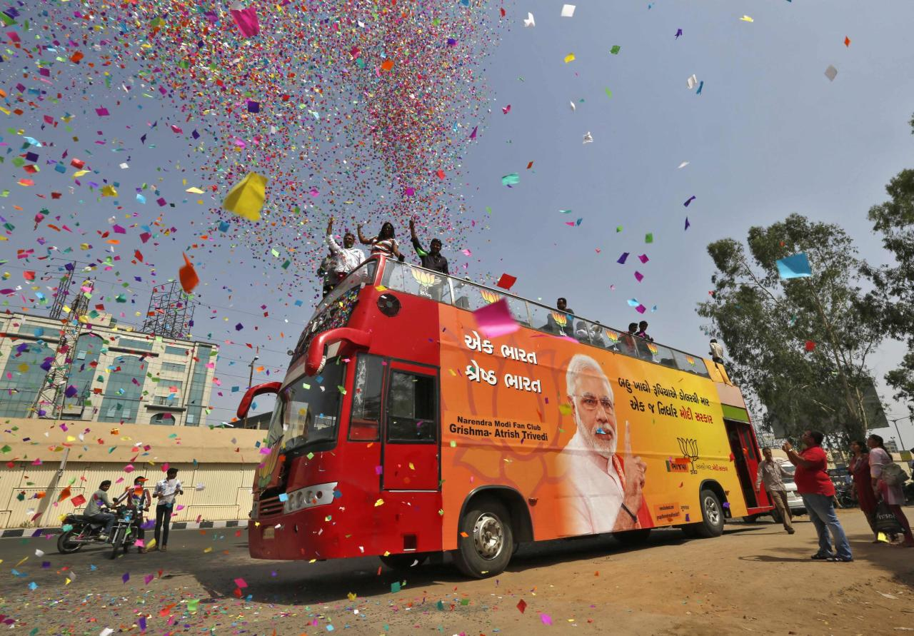 Supporters of Hindu nationalist Narendra Modi, the prime ministerial candidate for India's main opposition Bharatiya Janata Party (BJP), shower confetti from atop a bus in the western Indian city of Ahmedabad May 15, 2014. Modi is set to become India's next prime minister, according to a major exit poll released late on Wednesday, following others forecasting that his opposition party and its allies could win a parliamentary majority. The bus will be used during the party's celebrations on Friday, supporters said. REUTERS/Amit Dave (INDIA - Tags: POLITICS ELECTIONS TPX IMAGES OF THE DAY)
