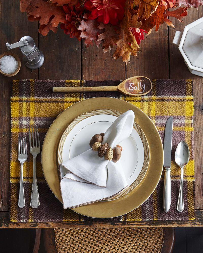 """<p>The hues of fall are on display in this warm and cozy table setting.</p><p><strong>To make:</strong> Start by cutting a vintage wool blanket into placemats. Drill holes in nuts and thread with wire or twine to create napkin rings. Finally pen guests names on new or vintage wooden spoons to create sweet place cards.</p><p><a class=""""link rapid-noclick-resp"""" href=""""https://www.amazon.com/NUTS-U-S-Hazelnuts-Artificial-Resealable/dp/B081ZLL331/ref=sr_1_1_sspa?tag=syn-yahoo-20&ascsubtag=%5Bartid%7C10050.g.2063%5Bsrc%7Cyahoo-us"""" rel=""""nofollow noopener"""" target=""""_blank"""" data-ylk=""""slk:SHOP NUTS"""">SHOP NUTS</a></p>"""