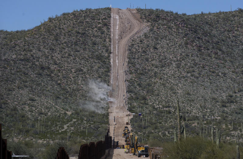 Construction crews perform a controlled detonation at the base of Monument Hill in Organ Pipe Cactus National Monument west of Lukeville, Ariz., on Wednesday, Feb. 26, 2020. Construction crews in southern Arizona have recently began blasting hills at the site to clear space for a new border wall system, bulldozing through a place called Monument Hill to construct a 30-foot (9-meter) steel wall along the U.S.-Mexico border. (Josh Galemore/Arizona Daily Star via AP)