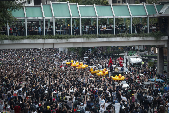 Large inflatable ducks, often associated with protests, are passed around the crowd at a pro-democracy rally in Bangkok, Thailand, Wednesday, Nov. 18, 2020. Police in Thailand's capital braced for possible trouble Wednesday, a day after a protest outside Parliament by pro-democracy demonstrators was marred by violence that left dozens of people injured. (AP Photo/Sakchai Lalit)