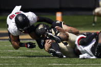 Wake Forest quarterback Sam Hartman is tackled by Louisville linebacker C.J. Avery and linebacker Jack Fagot during the first half of an NCAA college football game on Saturday, Oct. 2, 2021, in Winston-Salem, N.C. (AP Photo/Chris Carlson)