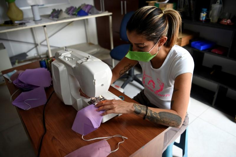 Clothing designer Stalina Svieykowsky uses a sewing machine to produce a face mask in a new business venture with her partner Nelson Jimenez as a response to the coronavirus disease (COVID-19), in San Antonio de los Altos