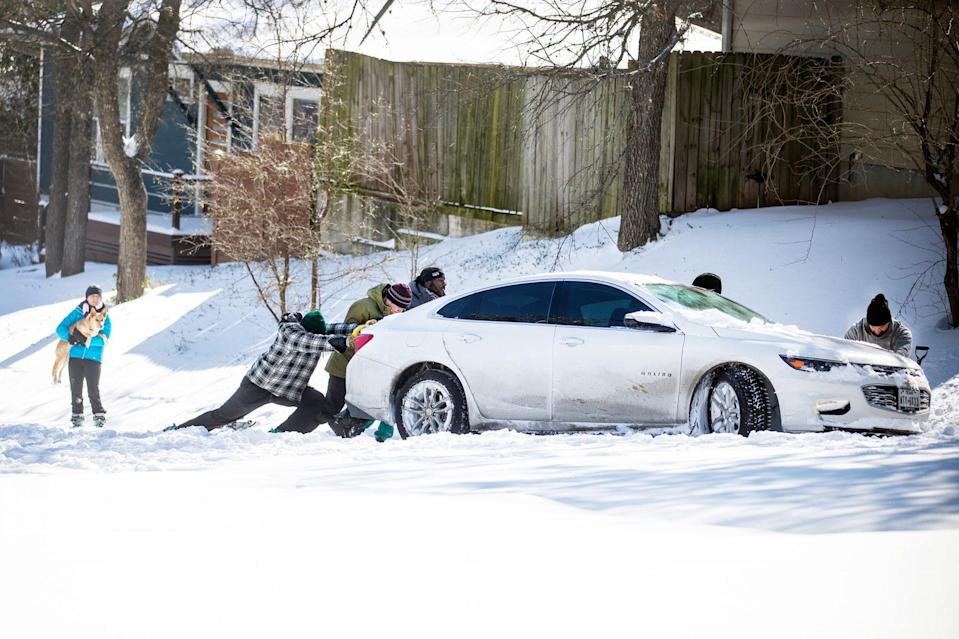 <p>People work together to push a car out of the snow in Austin, Texas, on Feb. 17. </p>