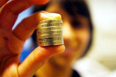 pound coins held between finger and thumb