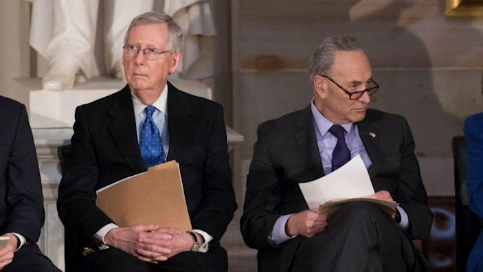 In this photo from Wednesday, Jan. 17, 2018, Senate Majority Leader Mitch McConnell, R-Ky., left, and Senate Minority Leader Chuck Schumer, D-N.Y., sit together to honor former Sen. Bob Dole, at the Capitol in Washington, Wednesday, Jan. 17, 2018. Schumer, arguably the most powerful Democrat in Washington, is trying to keep his party together to force a spending bill that would include protections for young immigrants, even as the federal government shutdown enters a third day. (AP Photo/J. Scott Applewhite)