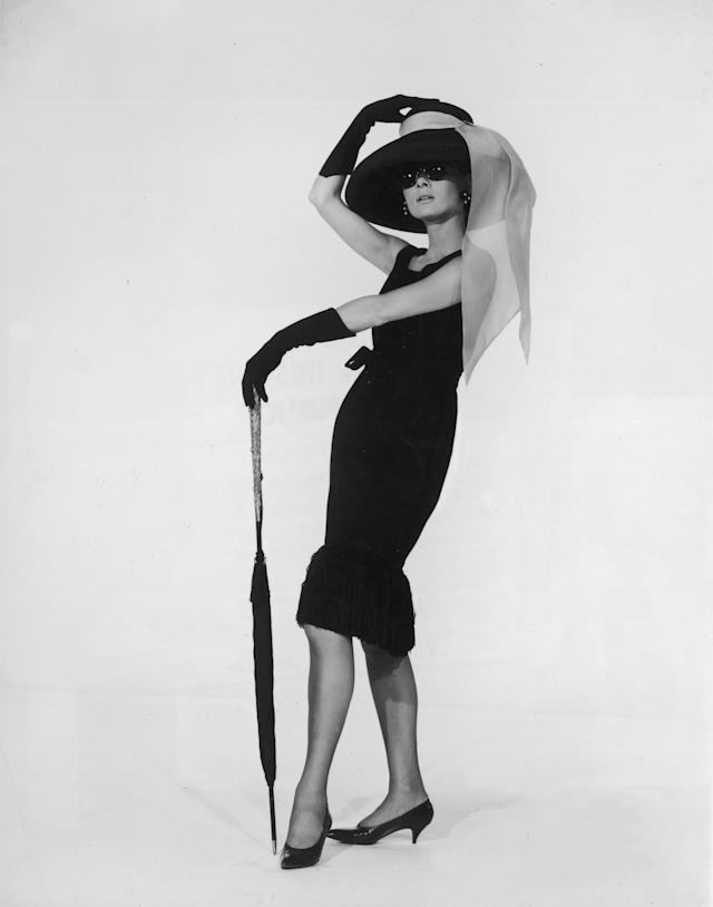 "Actress Audrey Hepburn wears the black cocktail dress designed by French couturier Hubert de Givenchy in a promotional portrait for ""Breakfast at Tiffany's."""