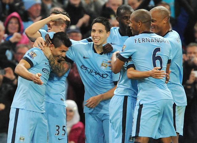 Manchester City's Sergio Aguero, left, celebrates with team mates after scoring against Liverpool during the English Premier League soccer match between Manchester City and Liverpool at the Etihad Stadium, in Manchester, England, Monday, Aug. 25, 2014. (AP Photo/Rui Vieira)