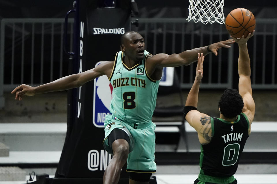 Boston Celtics forward Jayson Tatum shoots over Charlotte Hornets center Bismack Biyombo during the first half of an NBA basketball game on Sunday, April 25, 2021, in Charlotte, N.C. (AP Photo/Chris Carlson)