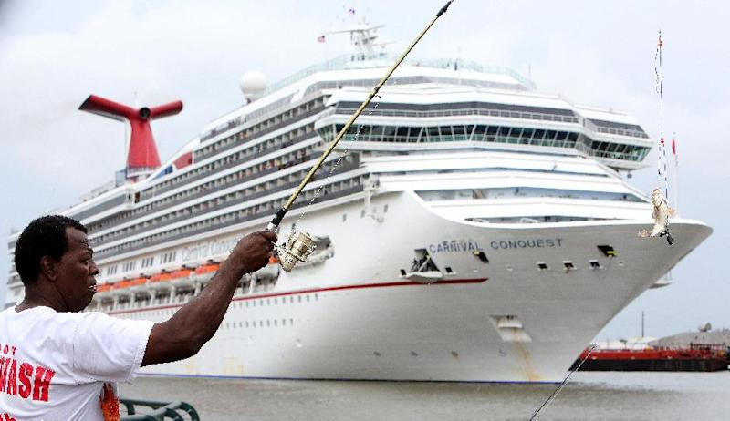 Clyde Hall of Mobile, Ala., catches a fish as the Carnival Conquest cruise ship moves down the Mobile River after turning around to dock at the Alabama Cruise Terminal on the Mobile River on a rainy Sunday, July 7, 2013, in downtown Mobile. The Conquest was diverted from New Orleans to Mobile after a tugboat sank in the Mississippi River Saturday, closing the river. (AP Photo/AL.com, Mike Brantley)