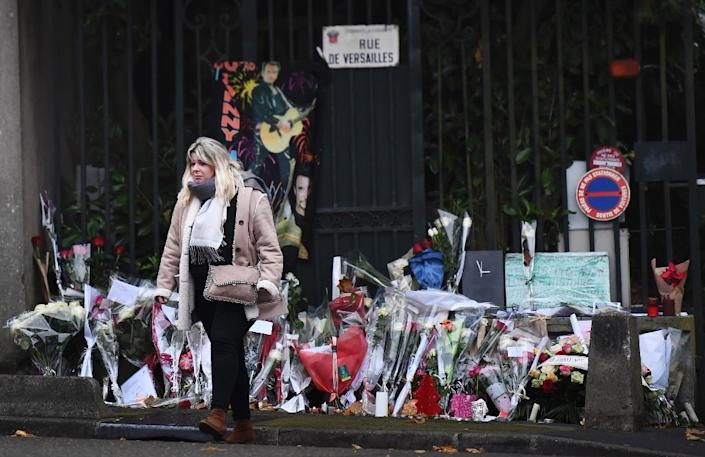 Fans deposed flowers outside the home of French rocker Johnny Hallyday in Marnes-la-Coquette, outside Paris, on Thursday (AFP Photo/Martin BUREAU)