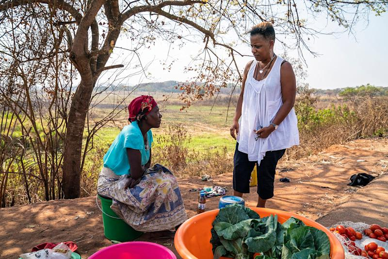 Deborah Barfield Berry, a reporter with USA TODAY, chats with a woman selling lettuce on the side of the road in Angola. A team from the paper was in the country this summer working on a package of stories for its 1619 slavery project.