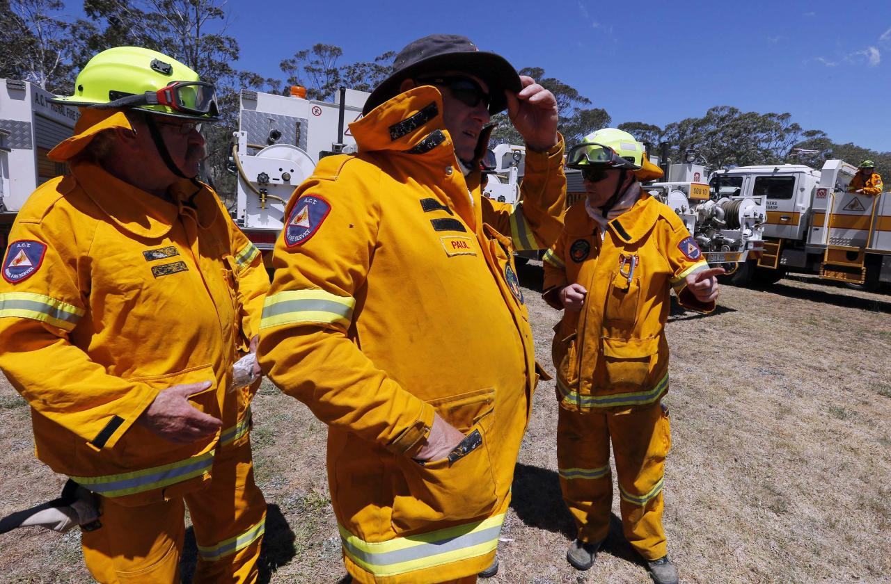 Rural Fire Service (RFS) firefighters watch a fire as it approaches homes near the Blue Mountains suburb of Blackheath, located around 70 km (43 miles) west of Sydney, October 23, 2013. A state of emergency has been declared in the Australian state of New South Wales, as bushfires continue to burn west of Sydney and weather conditions expected to worsen over the coming days. Around 60 fires are still burning across the state. REUTERS/David Gray (AUSTRALIA - Tags: ENVIRONMENT DISASTER)