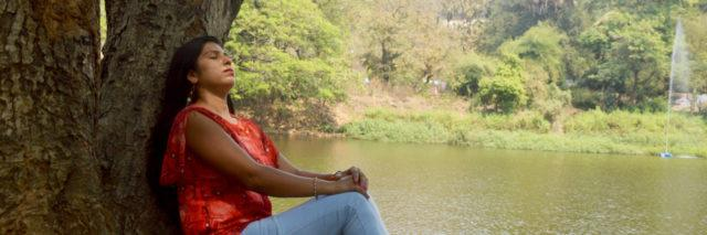 Indian woman sitting against a tree in a red shirt and blue jeans looking up with her eyes closed against the backdrop of a lake