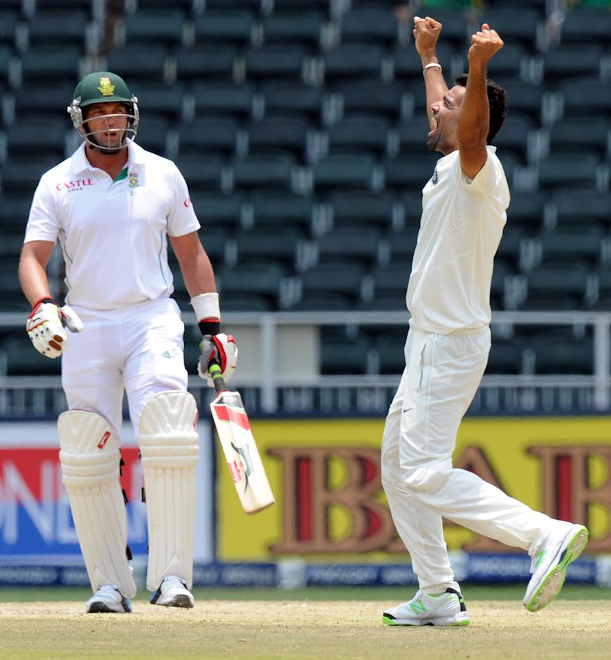 South African batsman (L) leaves after being bowled out by Indian bowler Zaheer Khan who is celebrating on the 5th day of a first cricket Test match between South Africa and India in Johannesburg at Wanderers Stadium on December 22, 2013.   AFP PHOTO