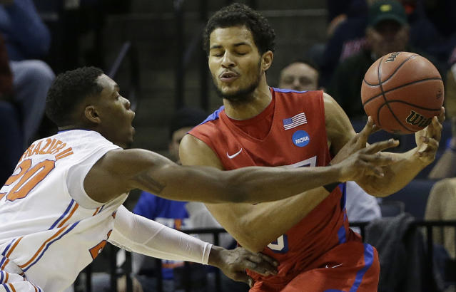 Dayton forward Devin Oliver (5) and Florida guard Michael Frazier II (20) work during the first half in a regional final game at the NCAA college basketball tournament, Saturday, March 29, 2014, in Memphis, Tenn. (AP Photo/Mark Humphrey)