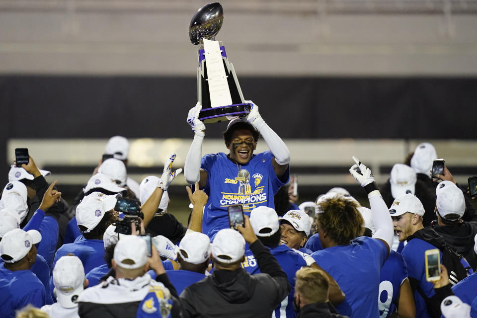 San Jose State cornerback Nehemiah Shelton holds the trophy while celebrating with teammates after defeating Boise State in an NCAA college football game for the Mountain West championship, Saturday, Dec. 19, 2020, in Las Vegas. (AP Photo/John Locher)