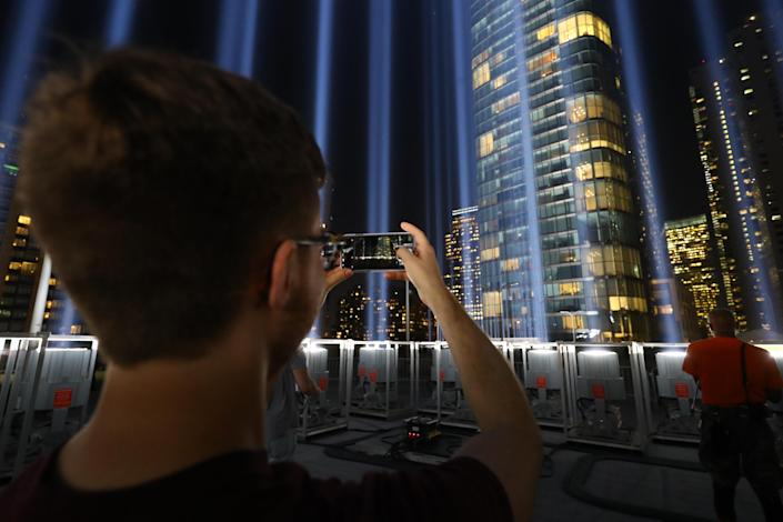 <p>A volunteer takes a photo of the Tribute in Light with his mobile device from the rooftop from which the beams of lights are projected on Sept. 5, 2018. (Photo: Gordon Donovan/Yahoo News) </p>