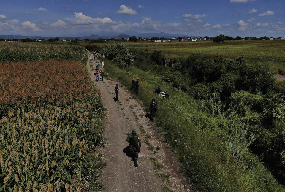Soldiers and police inspect an area were bodies are suspected of being buried on the outskirts of Cuautla, Mexico, Tuesday, Oct. 12, 2021. The government's registry of Mexico's missing has grown more than 20% in the past year and now approaches 100,000. (AP Photo/Fernando Llano)
