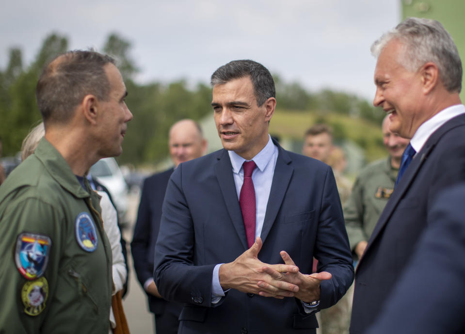 Spain's Prime Minister Pedro Sanchez, center, and Lithuanian President Gitanas Nauseda, right, speaks with Commander of the NATO's Baltic Air Policing Mission Lieutenant Colonel Bayardo Abos Alvares-Buiza, left, during a visit to the military air force base at Siauliai, some 220 kms (136,7 miles) east of the capital Vilnius, Lithuania, Thursday, July 8, 2021. (AP Photo/Mindaugas Kulbis)