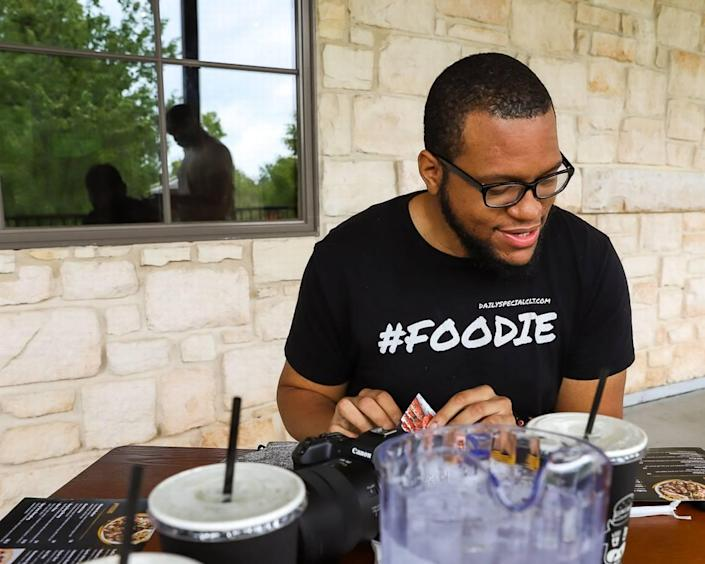 Cory Wilkins browses a menu for food and drink specials — his wheelhouse as @dailyspecialclt on Instagram.