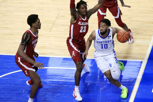 Kentucky's Davion Mintz (10) looks for help while defended by Alabama's John Petty Jr. (23) and Jordan Bruner, left, during the second half of an NCAA college basketball game in Lexington, Ky., Tuesday, Jan. 12, 2021. (AP Photo/James Crisp)