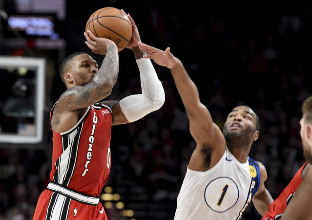 Portland Trail Blazers guard Damian Lillard, left, shoots the ball over Indiana Pacers forward T.J. Warren, right, during the second half of an NBA basketball game in Portland, Ore., Sunday, Jan. 26, 2020. Lillard scored 50 points as the Blazers won 139-129. (AP Photo/Steve Dykes)