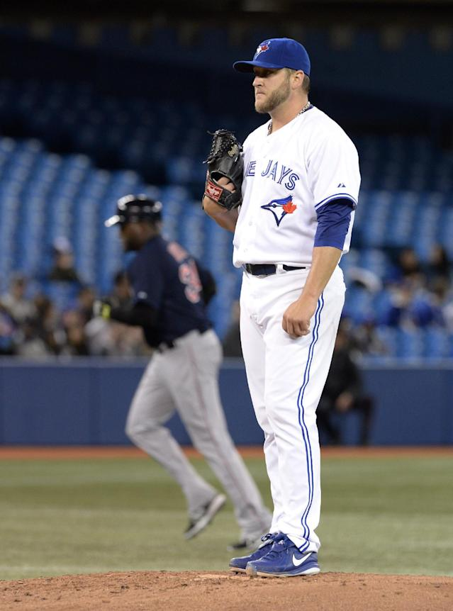 Toronto Blue Jays starting pitcher Mark Buehrle stands on the mound as Boston Red Sox's David Ortiz rounds the bases on a solo home run during the third inning of a baseball game in Toronto on Friday, April 25, 2014. (AP Photo/The Canadian Press, Frank Gunn)