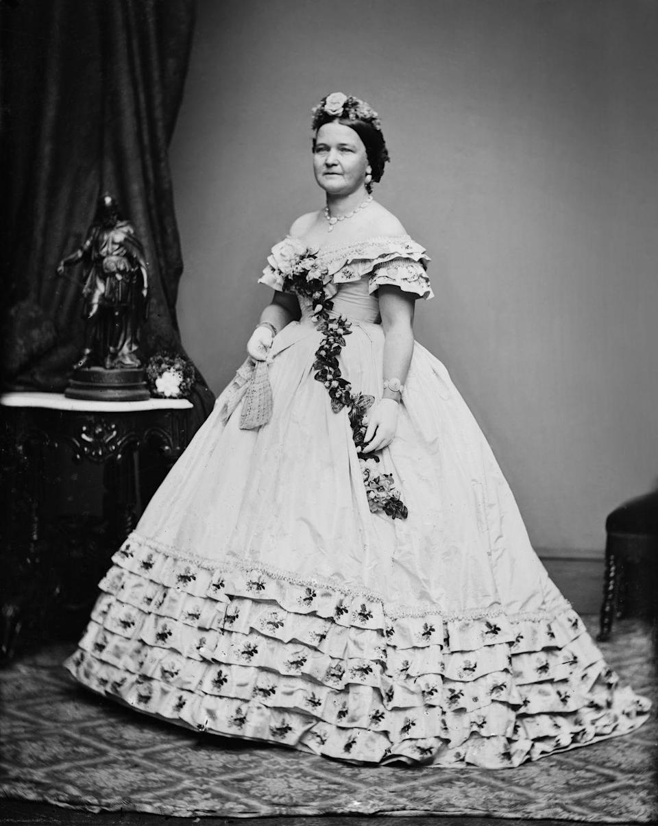 <p>Mary Todd Lincoln posed for a formal portrait in the off-the-shoulder floral ball gown she wore to her husband's inaugural ball in 1861. The First Lady paired the dress with a real floral sash and flower crown. </p>