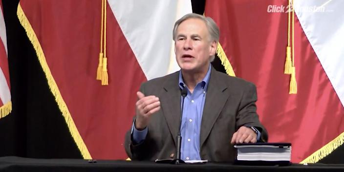 GOP Gov. Greg Abbott speaking at a border security press conference, with flags behind him.