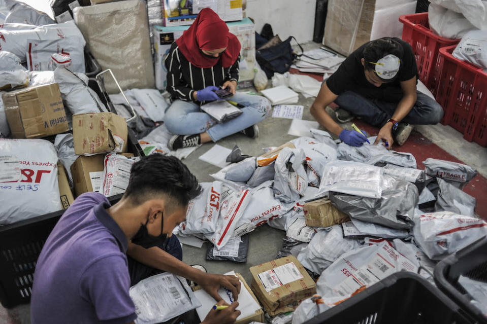 Staff of courier service company J&T Express check parcels that are ready for delivery at their warehouse in Seri Rampai April 7, 2020.  MCMC said as of October 2020, there are 109 courier service licence holders of various categories which are operating in Malaysia.— Picture by Shafwan Zaidon