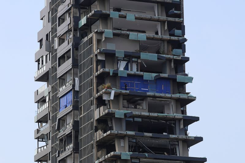 A man is seen on the balcony of a destroyed building, following a massive explosion, in Beirut