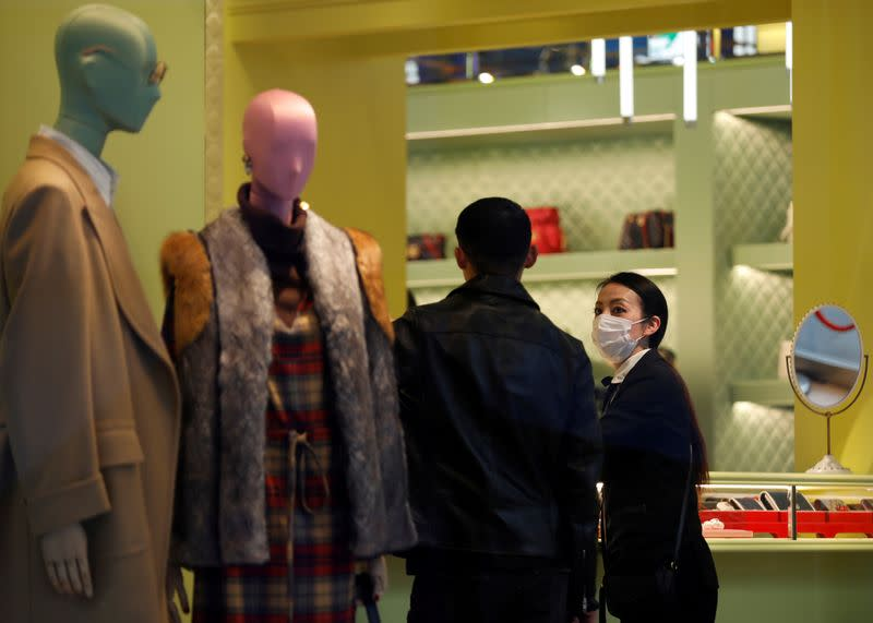 FILE PHOTO: A shop assistance wearing a protective face mask following an outbreak of the coronavirus talks to a customer at shopping mall in Tokyo