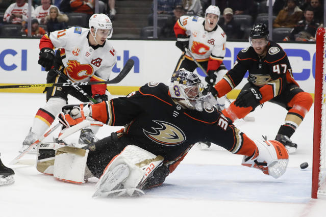 Calgary Flames center Mikael Backlund, left, scores past Anaheim Ducks goaltender John Gibson during the first period of an NHL hockey game in Anaheim, Calif., Thursday, Feb. 13, 2020. (AP Photo/Chris Carlson)