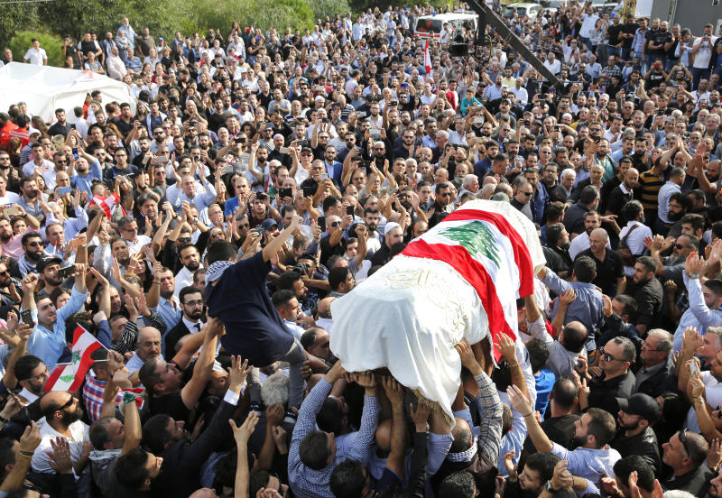 Mourners and relatives of Alaa Abu Fakher, who killed by a Lebanese soldier in Tuesday night protests in south of Beirut, carry his coffin during his funeral procession, in Choueifat neighborhood, Lebanon, Thursday, Nov. 14, 2019. For nearly a month, the popular protests engulfing Lebanon have been startlingly peaceful. But the shooting death of Fakher, a 38-year-old father by a soldier, the first such fatality in the unrest, points to the dangerous, dark turn the country could be heading into. (AP Photo/Hussein Malla)