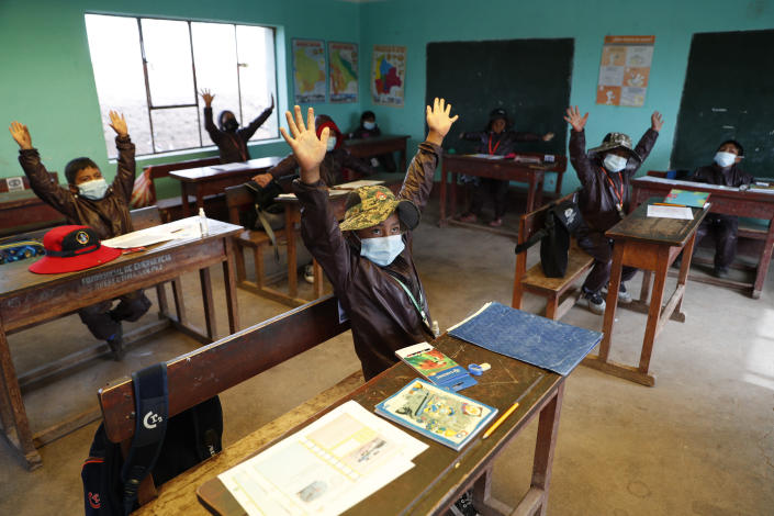 Aymaran Indigenous students raise their hands as they wear new, protective uniforms during the first week back to in-person classes amid the COVID-19 pandemic, near Jesus de Machaca, Bolivia, Thursday, Feb. 4, 2021. (AP Photo/Juan Karita)