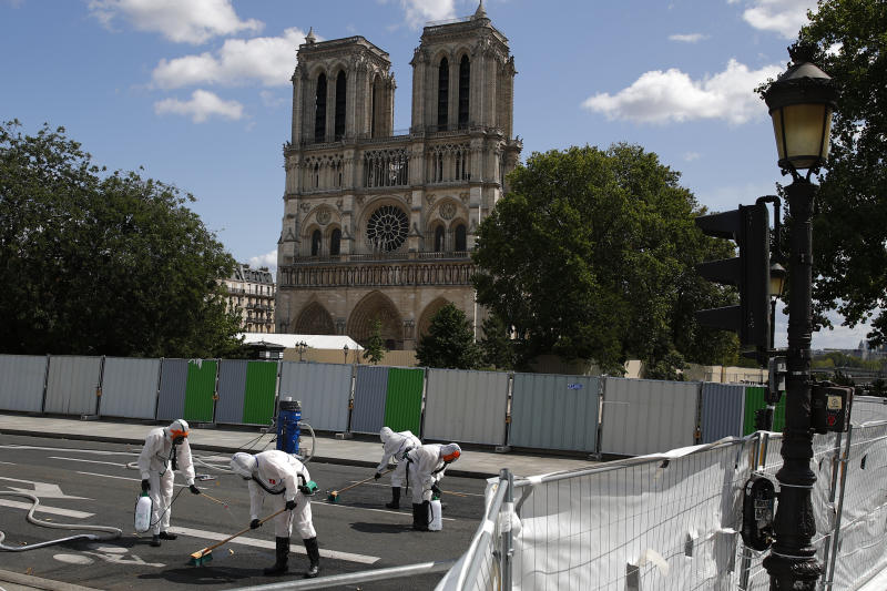 Workers clean the area in front of Notre Dame cathedral, Monday, Aug. 19, 2019 in Paris. Specialists shoring up fire-damaged Notre Dame Cathedral were returning to the Paris site on Monday for the first time in nearly a month, this time wearing disposable underwear and other protective gear after a delay prompted by fears of lead contamination. (AP Photo/Francois Mori)
