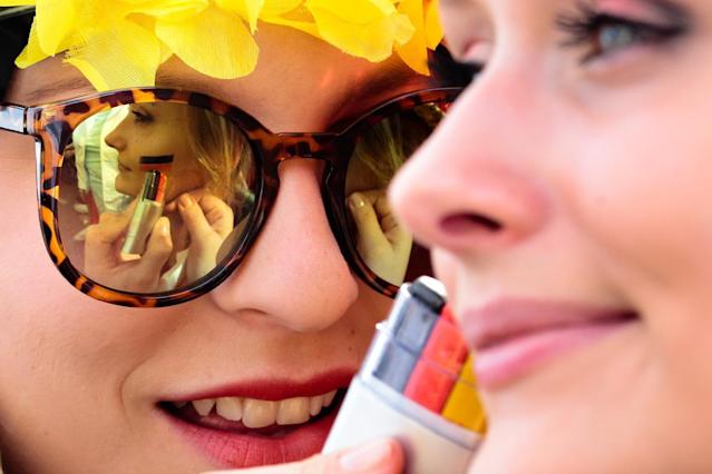 German soccer fans fix their make up with German colors prior to the kick off of their team's first game at the World Cup 2014 at a public viewing zone called 'fan mile' in Berlin, Monday, June 16, 2014. Germany plays against Portugal in group G match at the soccer World Cup 2014 in Brazil. (AP Photo/Markus Schreiber)