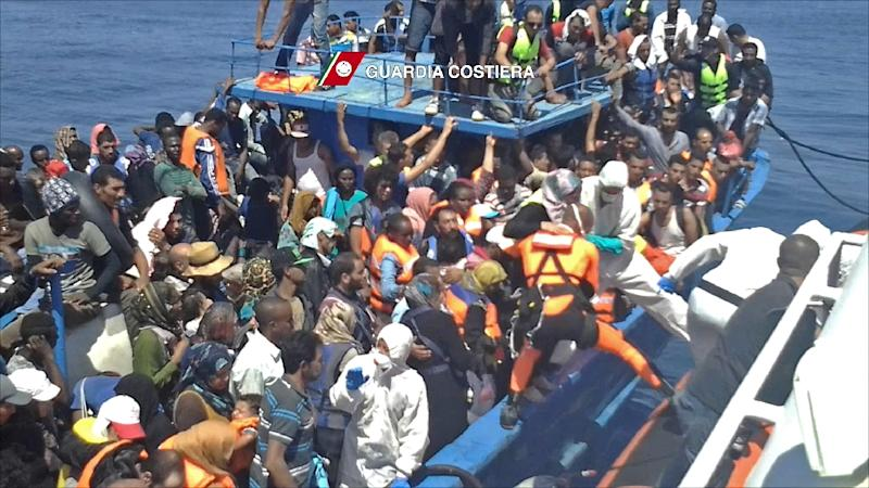 Migrants waiting on an overcrowded boat being helped during a rescue operation off the coast of Libya as part of the Frontex-coordinated Operation Triton