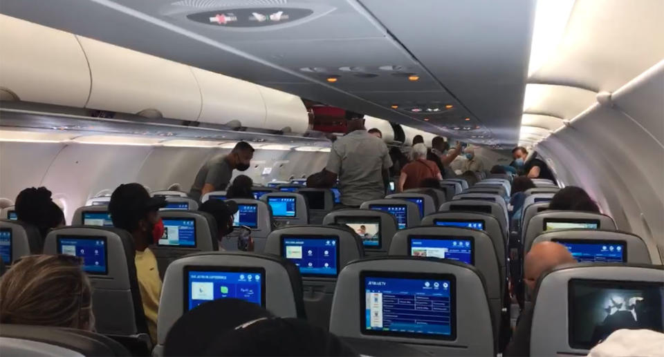 A still from a video shows passengers leaving a JetBlue aircraft because a toddler refused to wear a face mask.