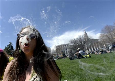 A woman blows smoke rings with marijuana smoke during the 4/20 Rally at the Civic Center in Denver